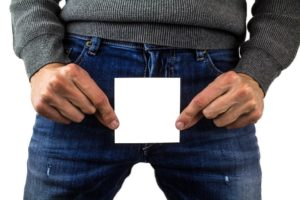 man wearing longsleeve and blue jeans holding a white paper in front of his private part
